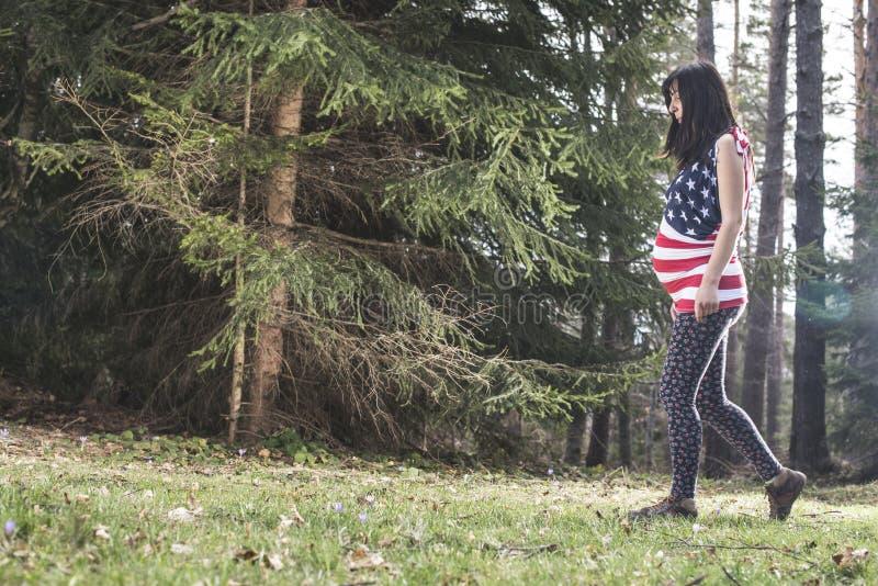 Mujer embarazada en el bosque imagenes de archivo