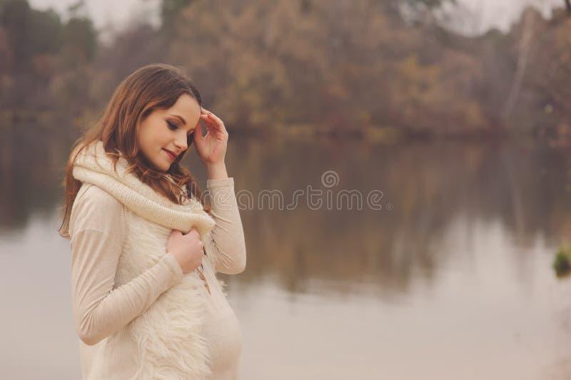 Mujer embarazada en el paseo al aire libre del otoño, humor caliente acogedor fotografía de archivo libre de regalías