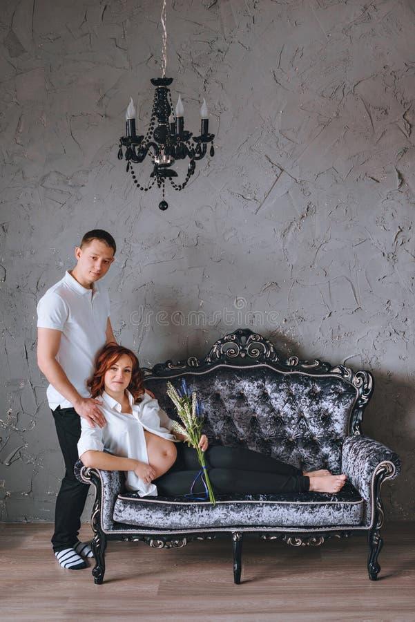 Mujer embarazada en el sofá gris Colocación al lado de su marido imagenes de archivo
