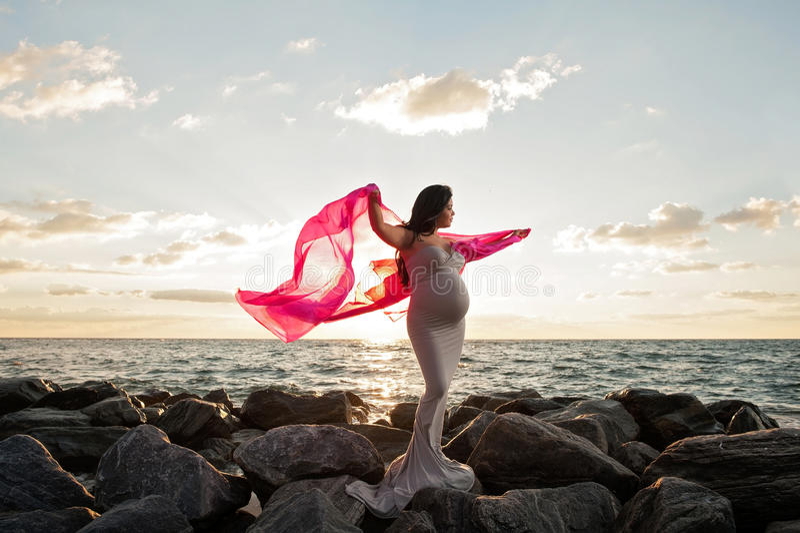 Mujer embarazada en la playa con velo rosado fotografía de archivo libre de regalías