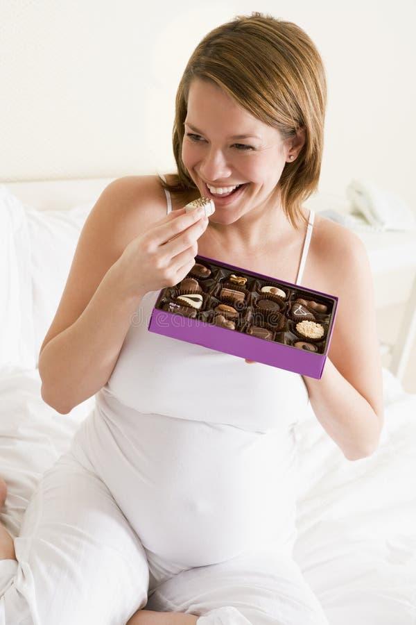 Mujer embarazada en la sonrisa del chocolate de la consumición de la cama fotos de archivo