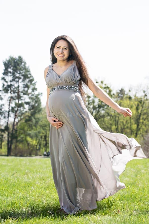 Mujer embarazada en un prado de la primavera imágenes de archivo libres de regalías