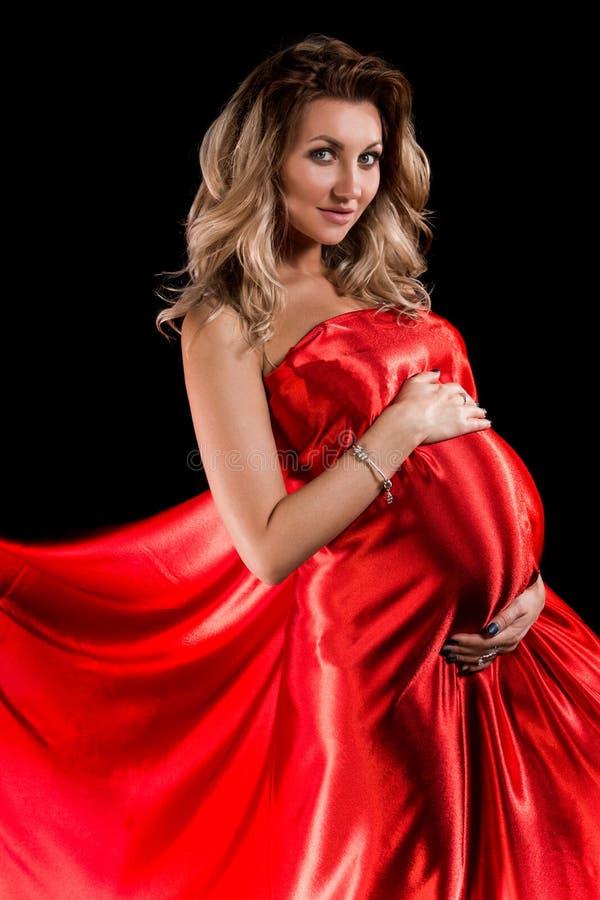 Mujer embarazada en una seda roja foto de archivo
