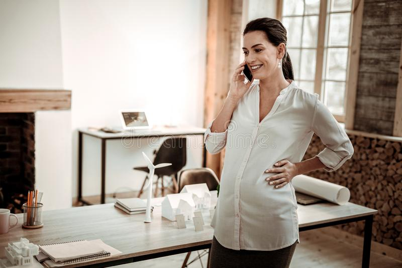 Mujer embarazada encantada que contesta a la llamada de teléfono imagen de archivo libre de regalías