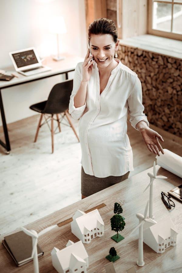 Mujer embarazada encantada que habla en el teléfono foto de archivo libre de regalías