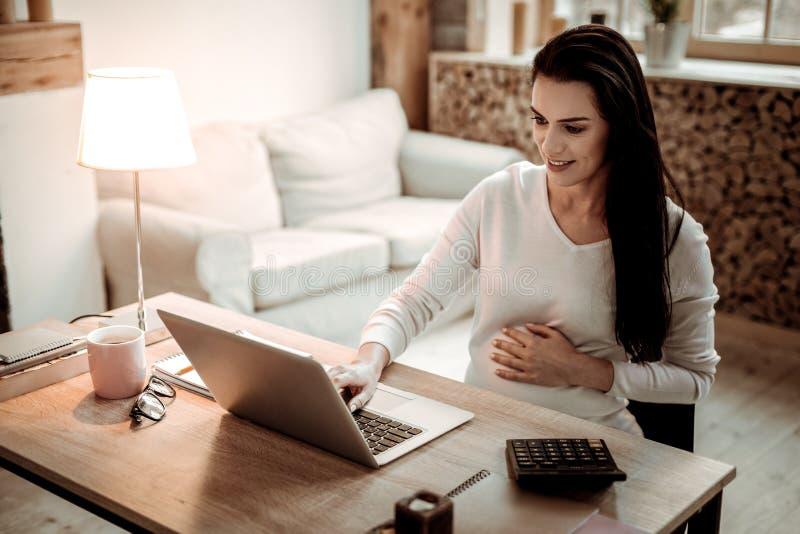 Mujer embarazada encantada que trabaja en el ordenador portátil foto de archivo