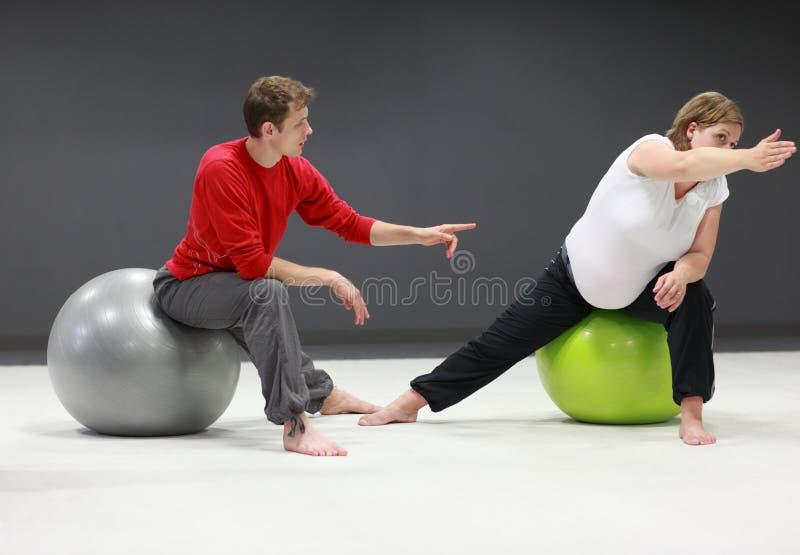 Mujer embarazada + entrenamiento personal del amaestrador imagen de archivo libre de regalías