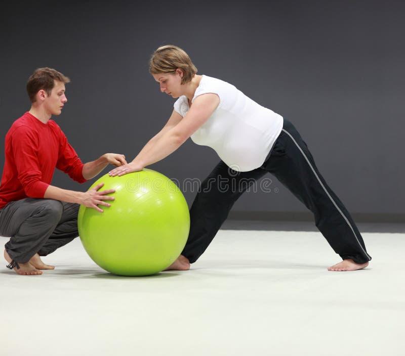 Mujer embarazada + entrenamiento personal del amaestrador imagenes de archivo