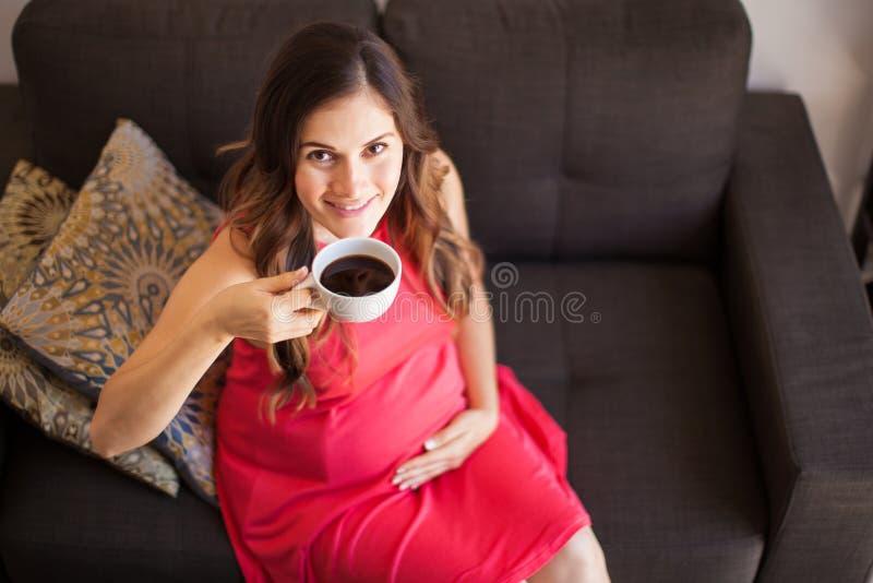 Mujer embarazada feliz con café fotos de archivo libres de regalías