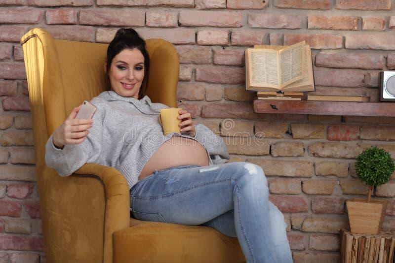 Mujer embarazada feliz en casa que se relaja en butaca imagenes de archivo