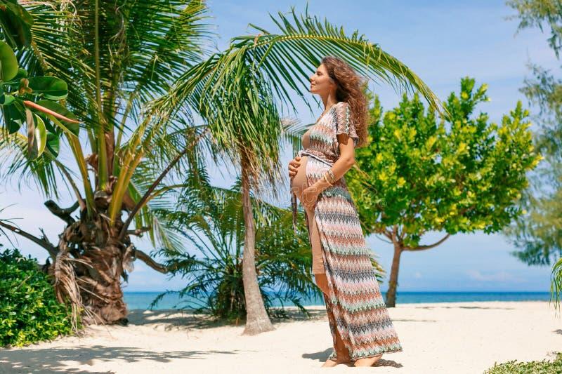 Mujer embarazada feliz joven hermosa en la playa tropical de la isla imágenes de archivo libres de regalías