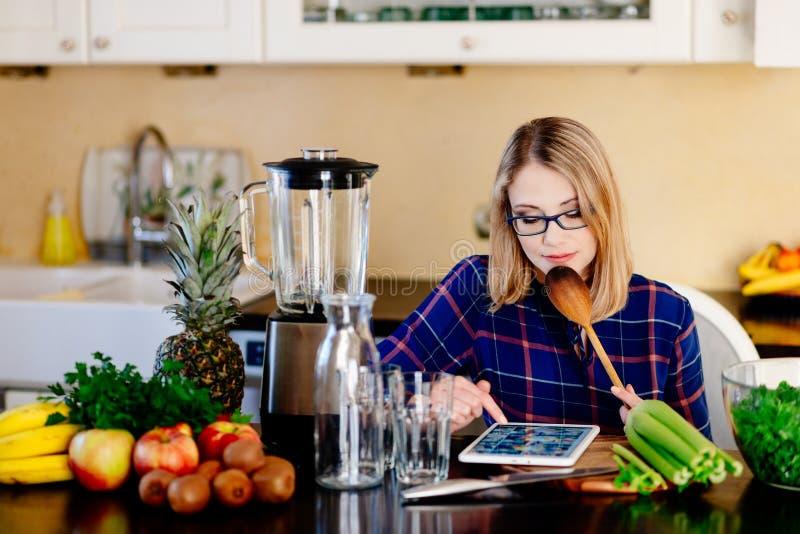 Mujer embarazada feliz joven que busca en Internet para la receta para el smoothie imagenes de archivo