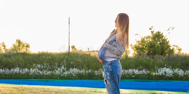 Mujer embarazada feliz joven que relaja y que disfruta de vida en naturaleza Tiro al aire libre Copyspace fotografía de archivo libre de regalías