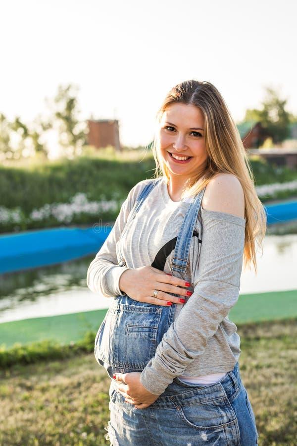 Mujer embarazada feliz joven que relaja y que disfruta de vida en naturaleza del otoño imagen de archivo