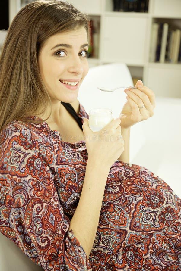 Mujer embarazada feliz que come el helado de chocolate en casa que mira la cámara imagen de archivo libre de regalías