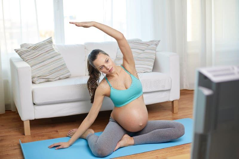 Mujer embarazada feliz que ejercita en casa imágenes de archivo libres de regalías
