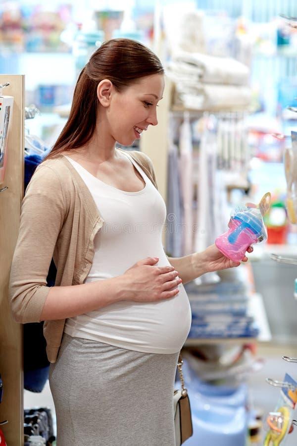 Mujer embarazada feliz que elige el biberón en la tienda foto de archivo