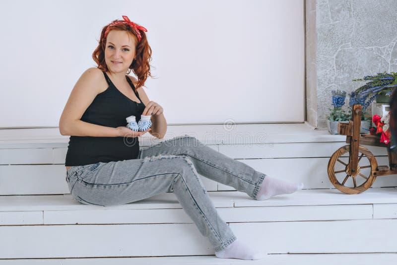 Mujer embarazada feliz que lleva a cabo botines, con un vendaje rojo en su cabeza En un fondo ligero Jóvenes pelirrojos del embar fotos de archivo libres de regalías