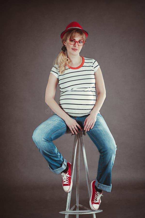 Mujer embarazada feliz que mira su vientre desnudo imagen de archivo