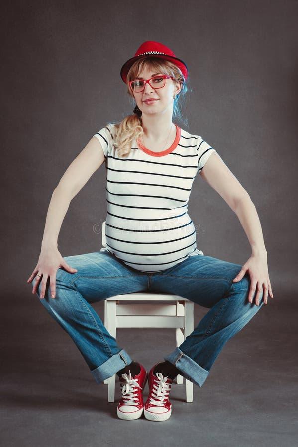Mujer embarazada feliz que mira su vientre desnudo imagenes de archivo
