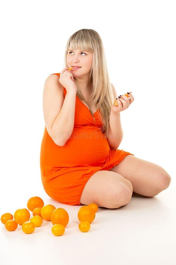 Mujer embarazada feliz que se sienta con las naranjas foto de archivo