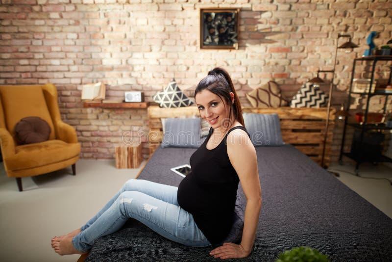Mujer embarazada feliz que se sienta en cama en casa imagen de archivo libre de regalías