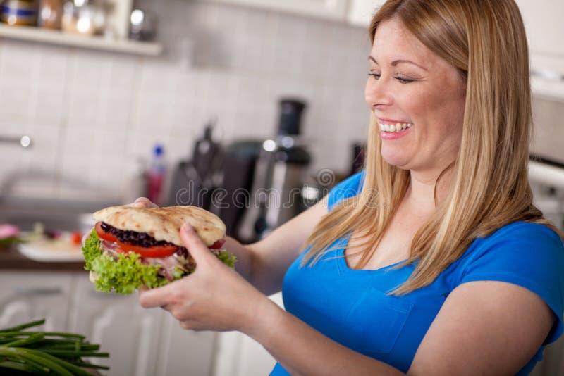 Mujer embarazada hambrienta que come una hamburguesa grande, comida basura foto de archivo