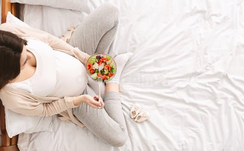 Mujer embarazada hambrienta que goza de la ensalada de las verduras frescas en cama foto de archivo