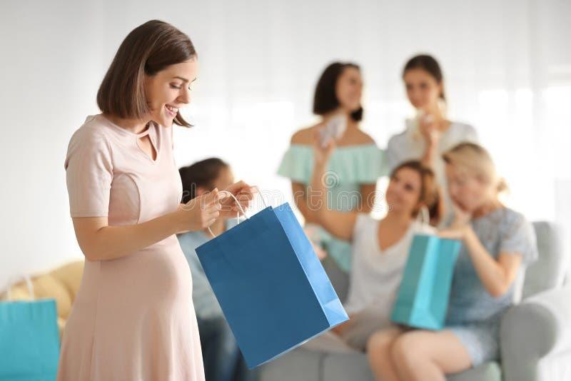 Mujer embarazada hermosa con la bolsa de papel en el partido de fiesta de bienvenida al bebé imagen de archivo