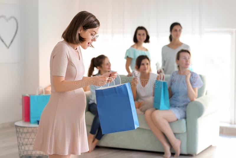 Mujer embarazada hermosa con la bolsa de papel en el partido de fiesta de bienvenida al bebé fotografía de archivo