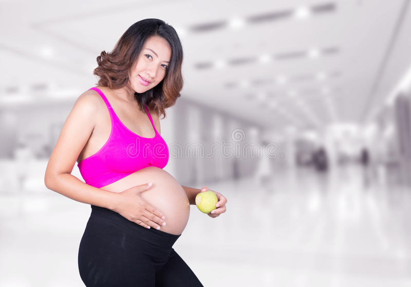 Mujer embarazada hermosa con la manzana verde en hospital imagenes de archivo