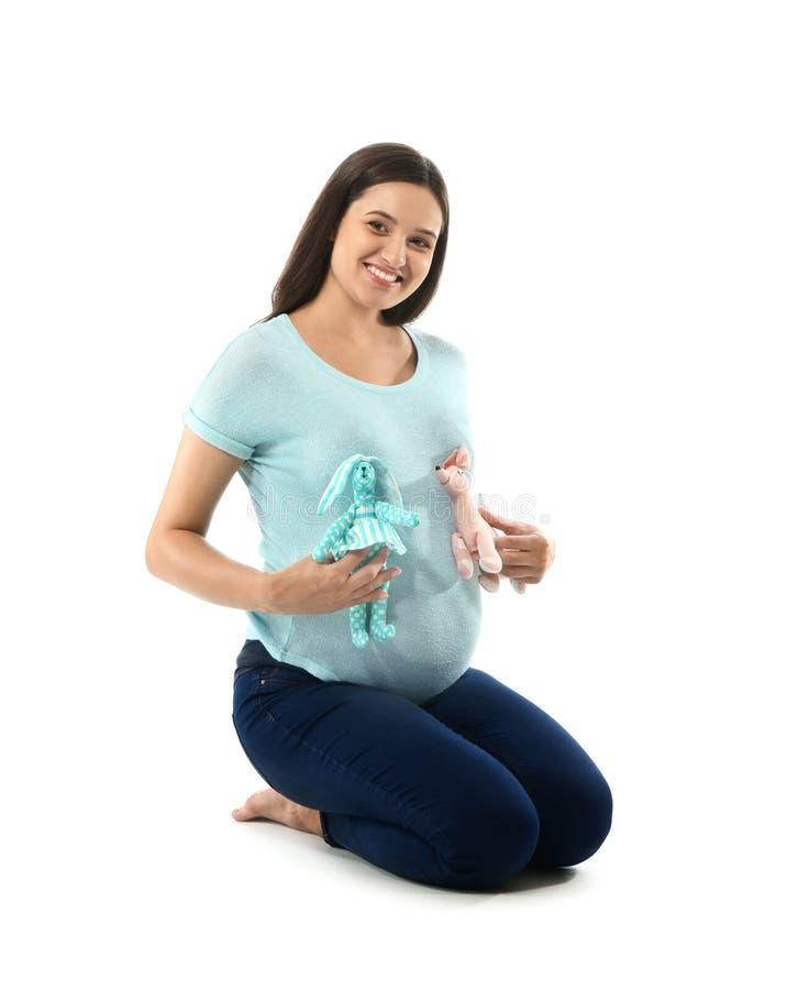 Mujer embarazada hermosa con los juguetes azules y rosados en el fondo blanco foto de archivo libre de regalías