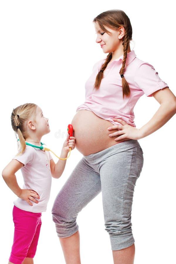 Mujer embarazada hermosa con su hija. fotos de archivo