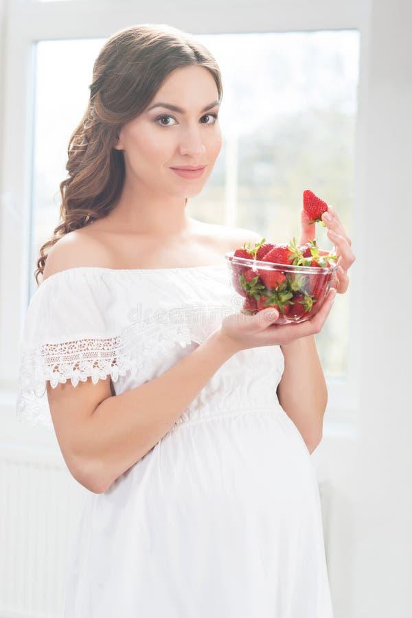 Mujer embarazada hermosa con un cuenco de fresas foto de archivo libre de regalías