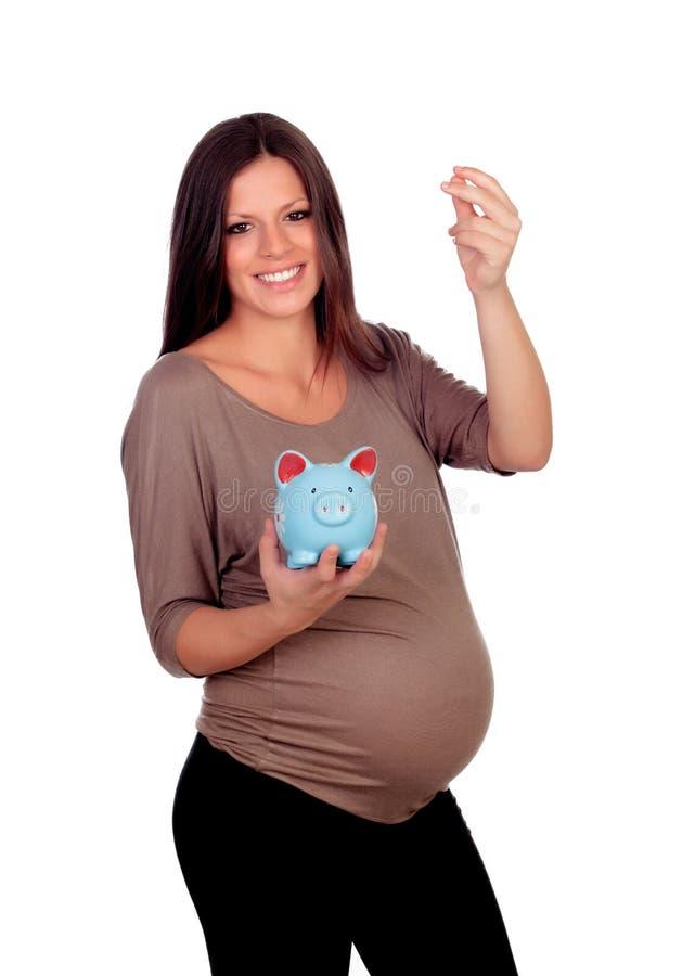 Mujer embarazada hermosa con un moneybox azul fotografía de archivo libre de regalías
