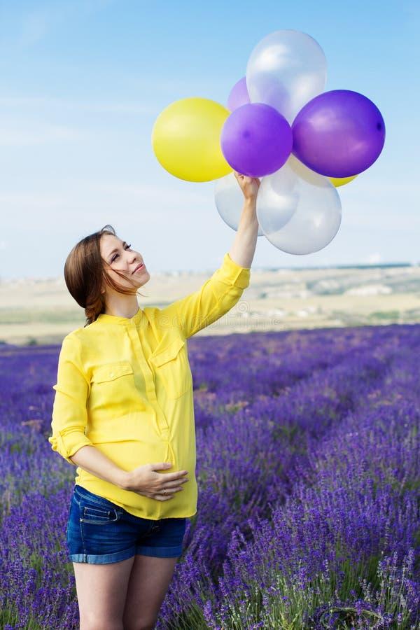 Mujer embarazada hermosa en el campo de la lavanda fotos de archivo libres de regalías