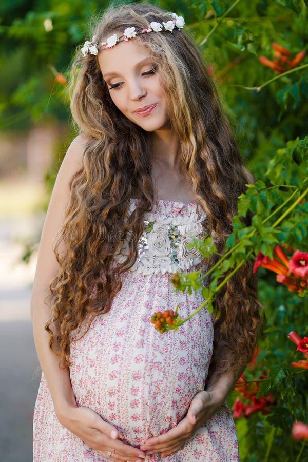 Mujer embarazada hermosa en el parque imagenes de archivo