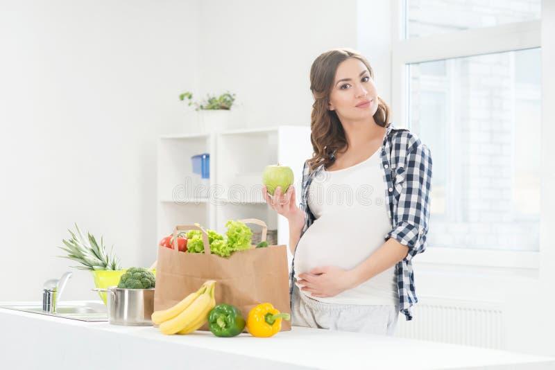 Mujer embarazada hermosa en la cocina fotos de archivo libres de regalías