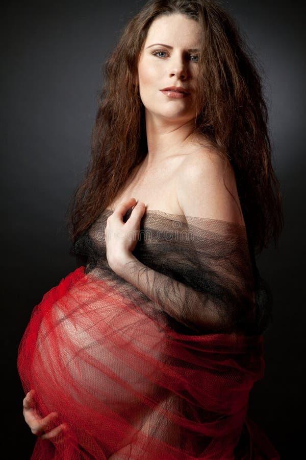 Mujer embarazada hermosa con el pelo rizado largo. imagenes de archivo