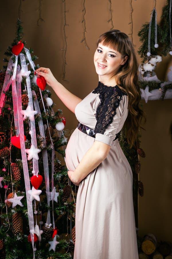 Mujer embarazada hermosa joven en un vestido largo cerca del Año Nuevo tr imágenes de archivo libres de regalías