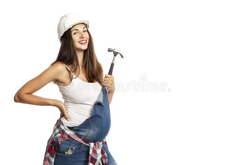 Mujer embarazada hermosa joven en vaqueros y la sonrisa del casco de la construcción En las manos de una herramienta de la constr fotografía de archivo