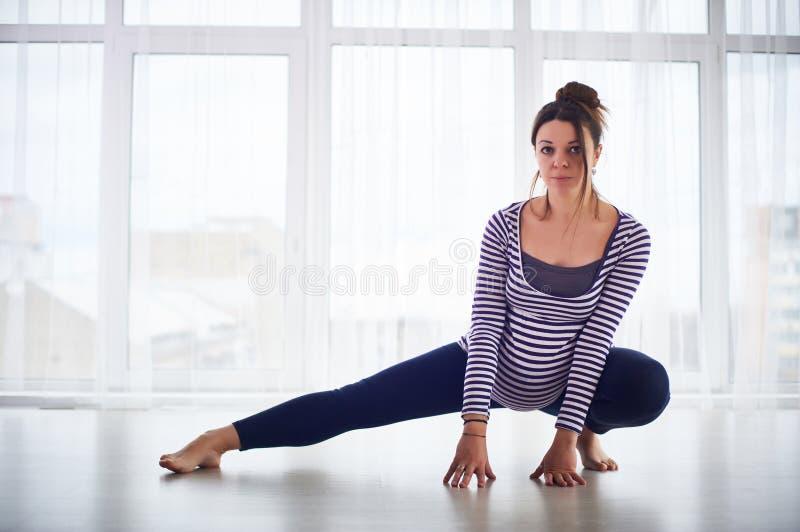 Mujer embarazada hermosa joven que hace asana de la yoga en casa imágenes de archivo libres de regalías