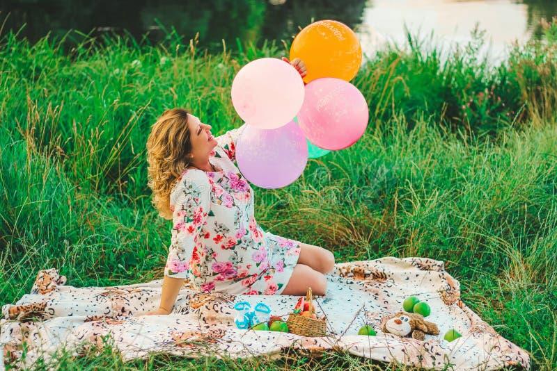 Mujer embarazada hermosa joven que se sienta en una comida campestre en una manta en el parque con los globos coloridos en primer foto de archivo libre de regalías