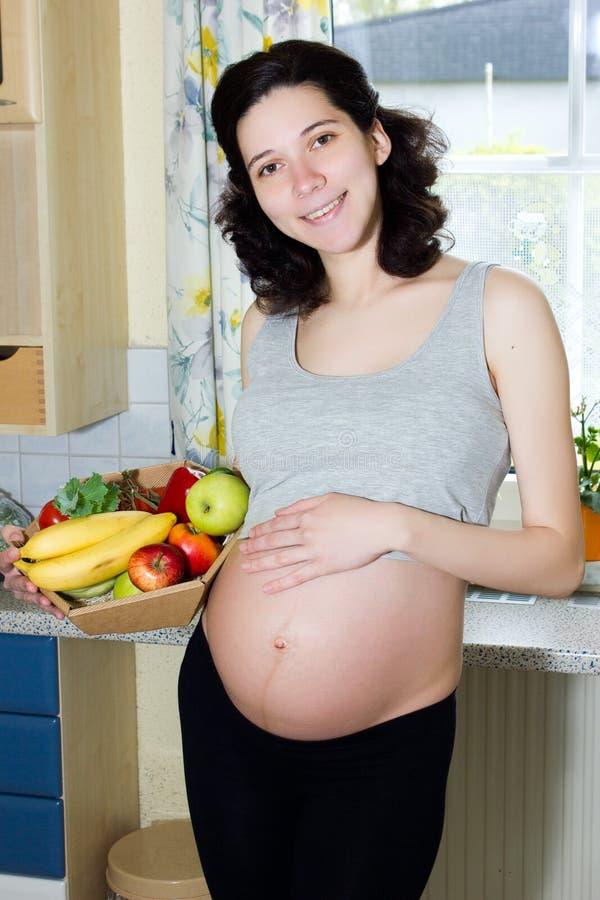 Mujer embarazada hermosa joven que sostiene una cesta de frutas imagenes de archivo