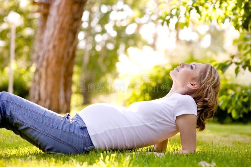 Mujer embarazada hermosa que miente en la hierba en día soleado Lookin imagenes de archivo