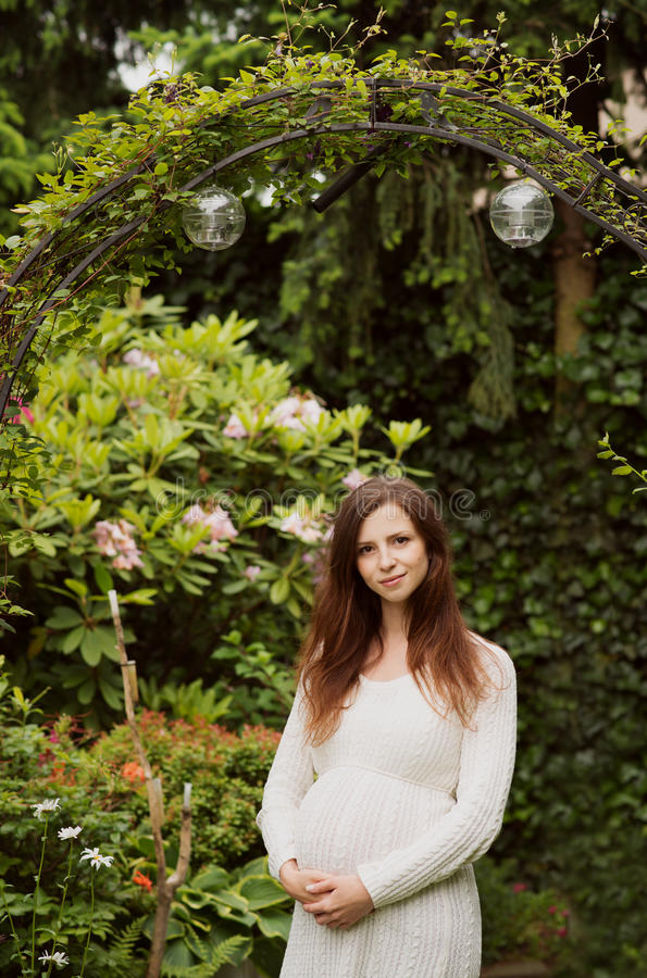 Mujer embarazada hermosa que se coloca en jardín imagen de archivo libre de regalías