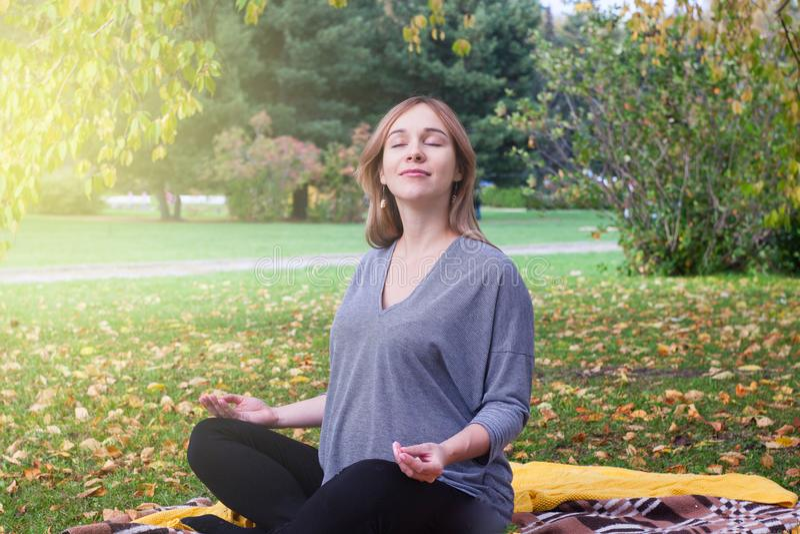 Mujer embarazada hermosa que se relaja y que sonríe en parque del otoño imágenes de archivo libres de regalías