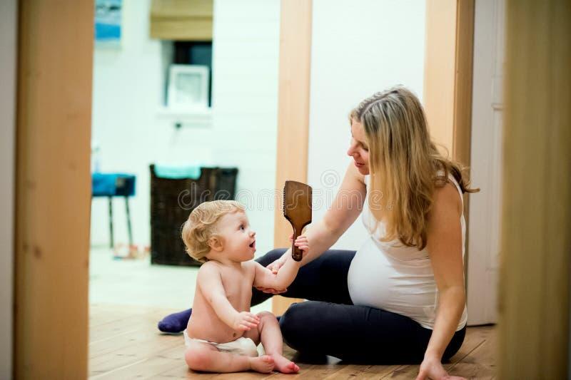Mujer embarazada hermosa que se sienta con un niño pequeño en el piso en casa foto de archivo