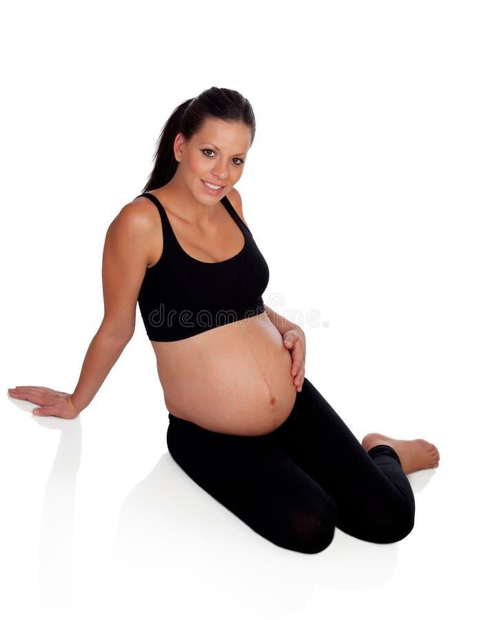 Mujer embarazada hermosa que se sienta en el suelo imagen de archivo libre de regalías
