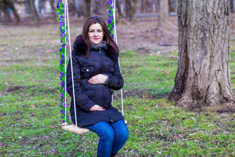 Mujer embarazada hermosa que toca su vientre con las manos imagen de archivo